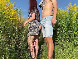 Sex with his wife on the field with flowers. Public place